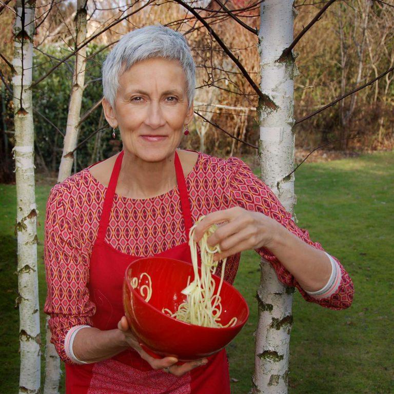 Thea mit gelben Zucchinis in roter Schüssel unter jungen Birken